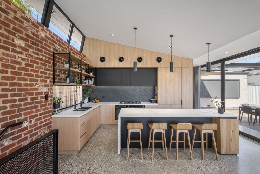 The kitchen features a beautiful accent wall made from recycled bricks