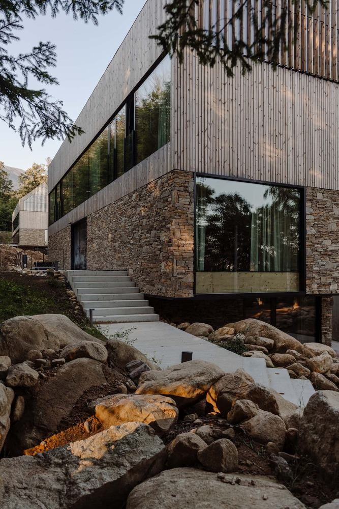 The area around the buildings is landscaped with stone which is also found in the design of the facades
