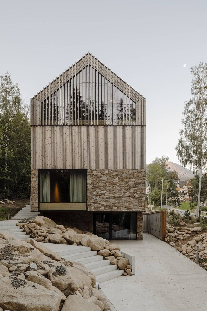 The gable roof is clad in wood just like the exterior walls and the side section features vertical fins