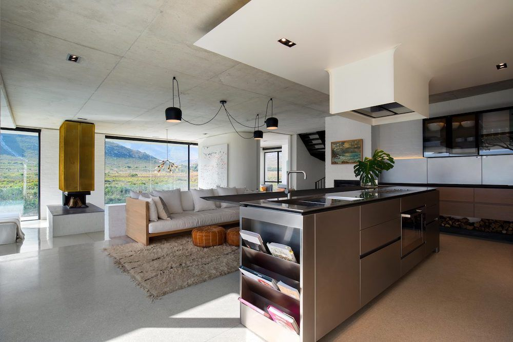 The island ensures a smooth transition between the kitchen and the lounge area, especially considering its bar extension