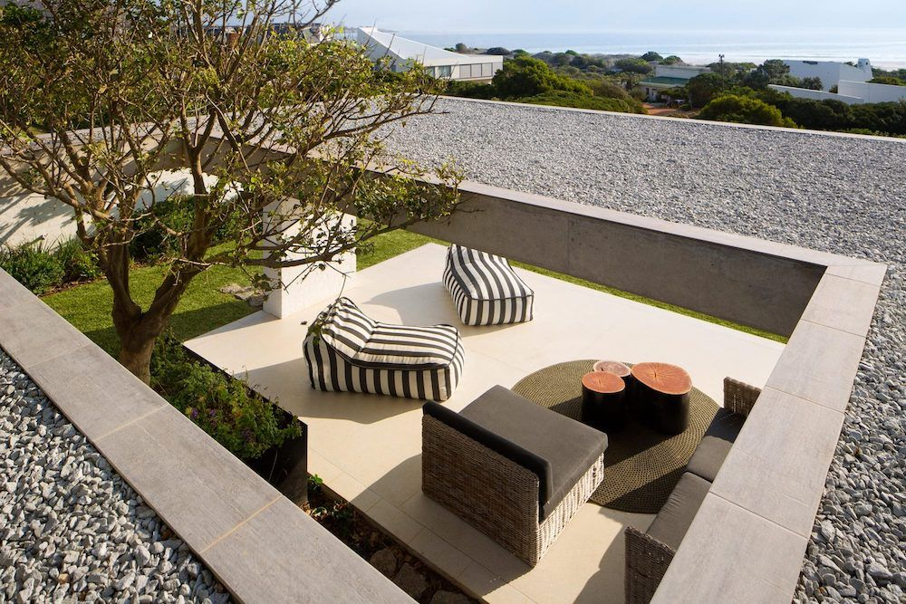 The outdoor living spaces are framed by columns and sheltered by roofs without feeling too artificial or disconnected from nature