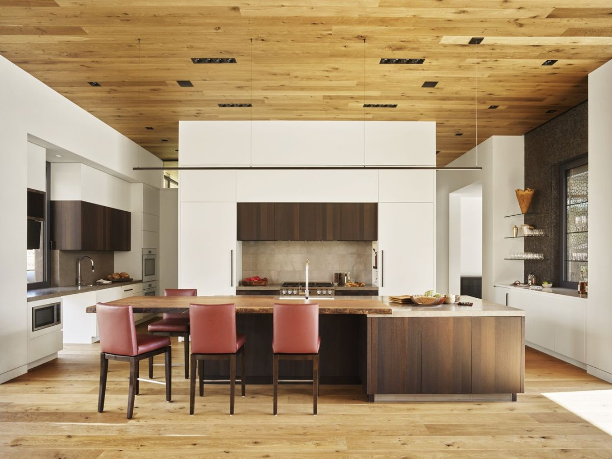 The kitchen, dining area and the living share an open plan space with wooden floors and matching ceilings