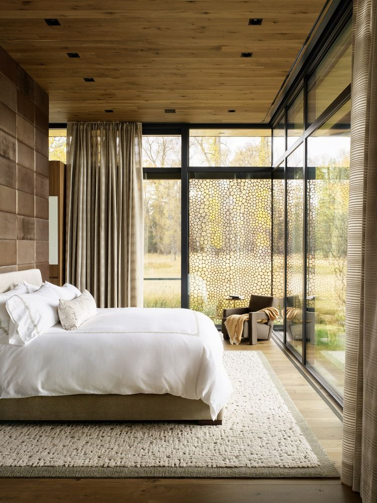 Full-height glass walls and windows open up the spaces towards the serene surroundings