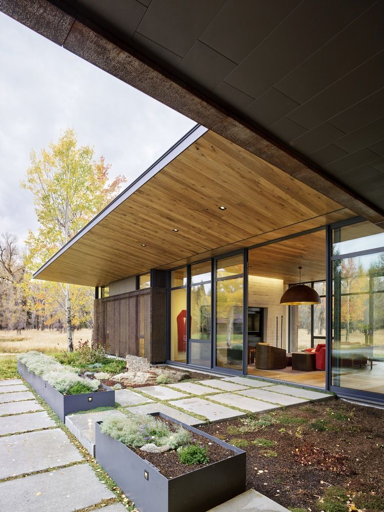 In the context of the L-shaped floor plan, the garage occupies the smaller side and the social areas the other