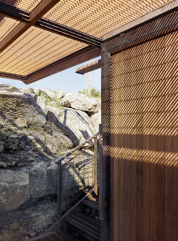 The earthy, rust-like colors allow the cabin to blend with the vernacular