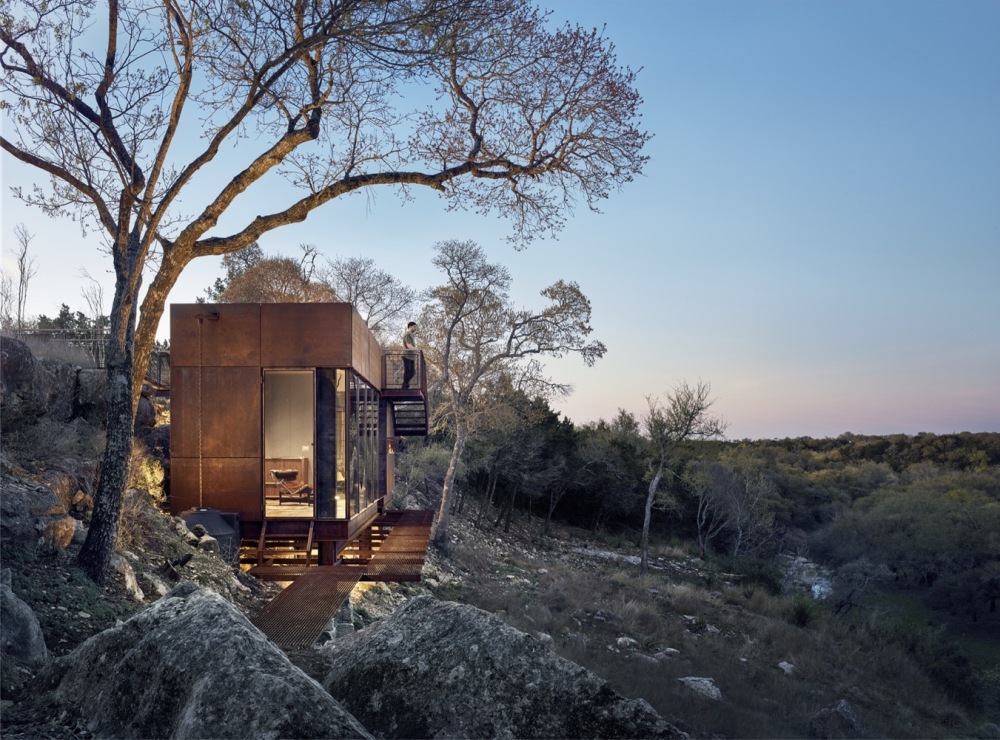 The cabin is oriented towards the valley and has big windows that frame the view