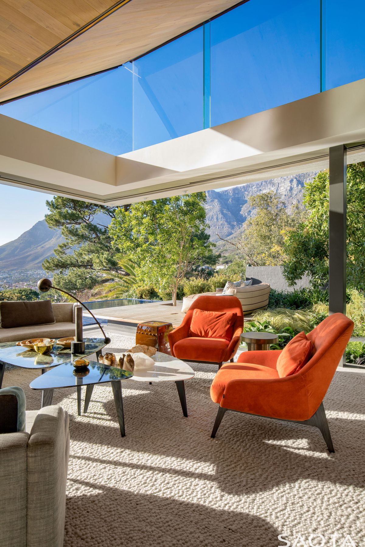 The lounge area is framed by seamless, panoramic views and features two eye-catching and comfy armchairs