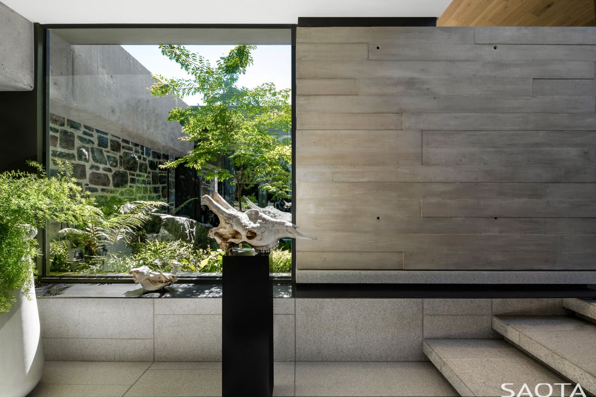 The entrance lobby is visibly connected to the outdoors through a large window facing the courtyard