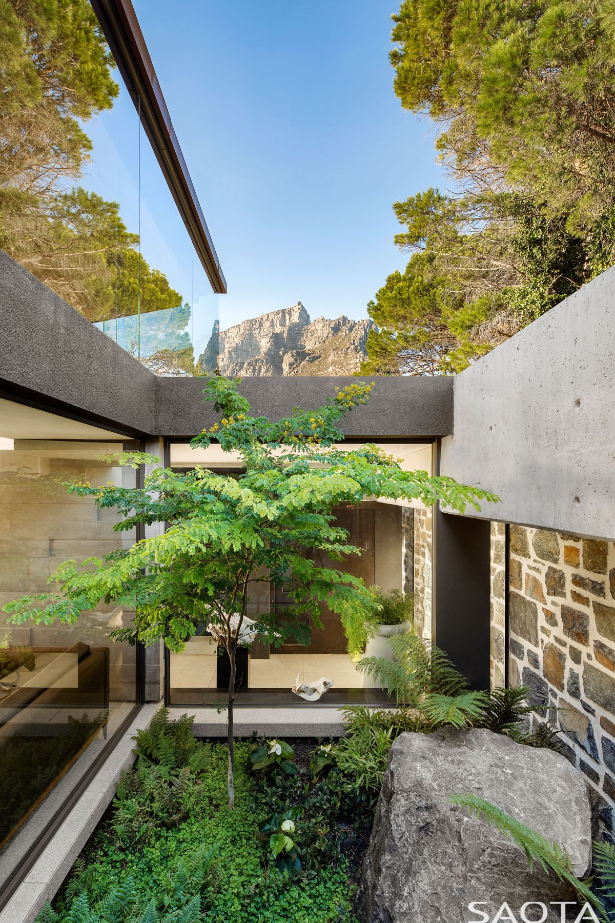 A secret courtyard is contained between the house and the stone wall. It's the link between the internal areas and the outside world