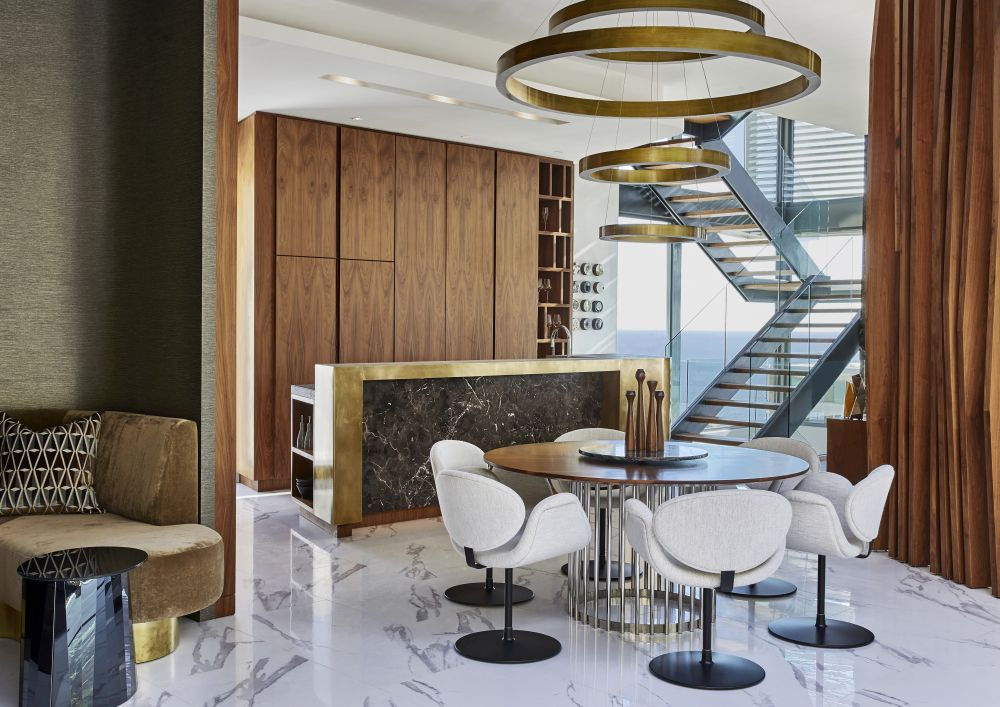 The double-volume glass staircase brings in abundant natural light while also exposing the panoramic views