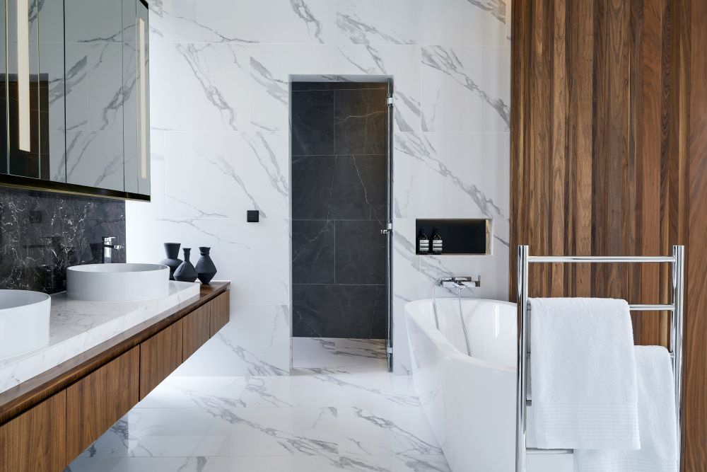 dark and white marble seamlessly blend with each other in the bathroom where they're complemented by wooden surfaces