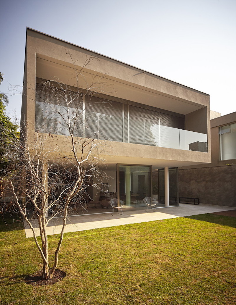 This urban house is situated on a flat and simple plot of land with close neighboring buildings