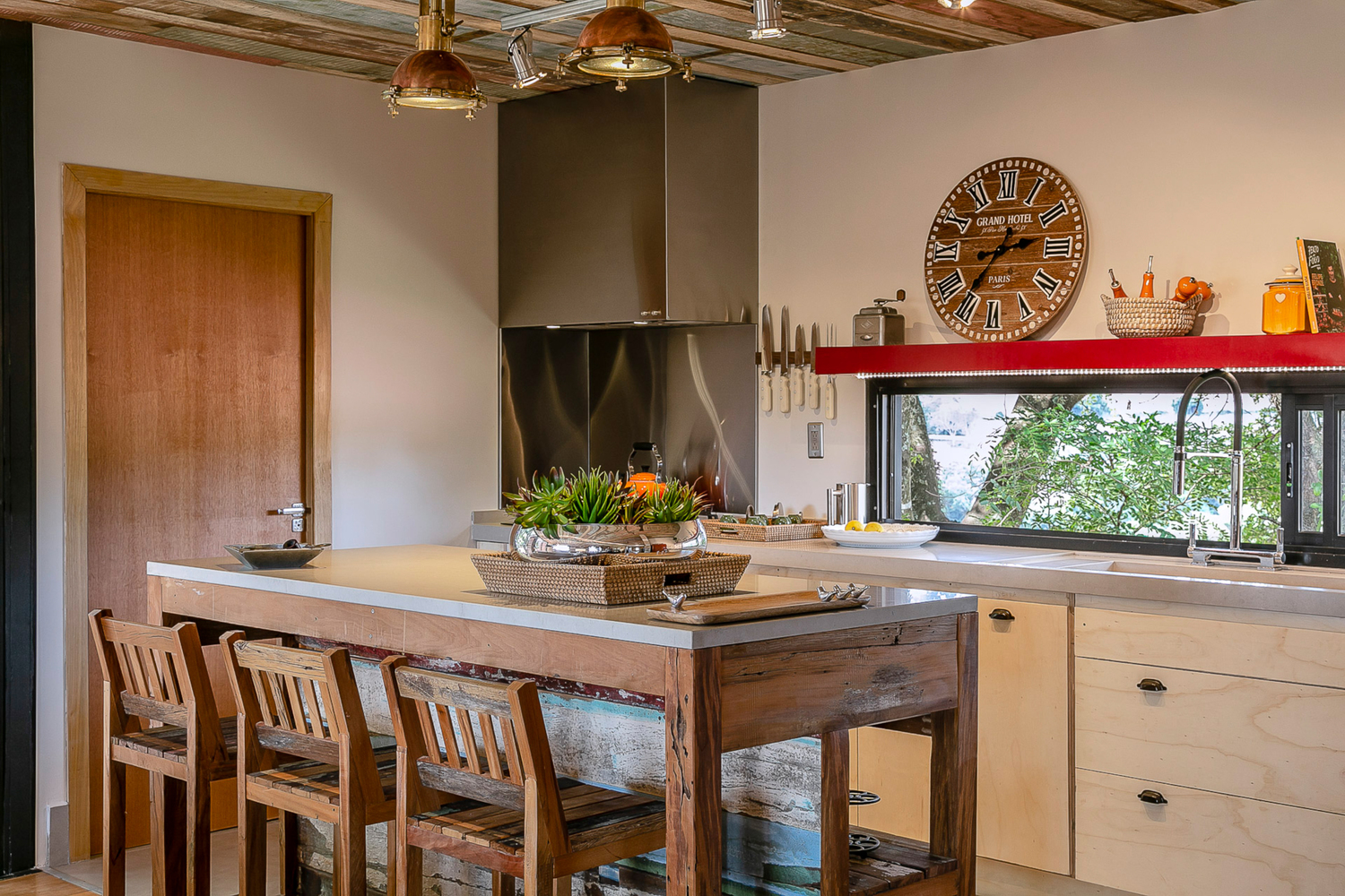 The kitchen features a horizontal backsplash window which offers a view of the tree canopies