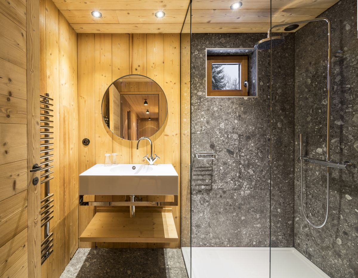 The bathroom is compact, with wood and marble surfaces and a clear glass walk-in shower