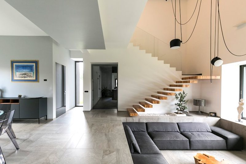 A set of floating stairs is positioned adjacent to the sunken lounge area, connecting the ground floor to the upper level