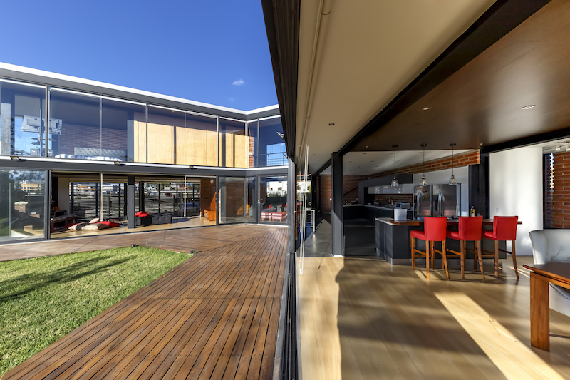 The internal spaces extend outside onto wooden decks and patios which outline the unusual shape of the building