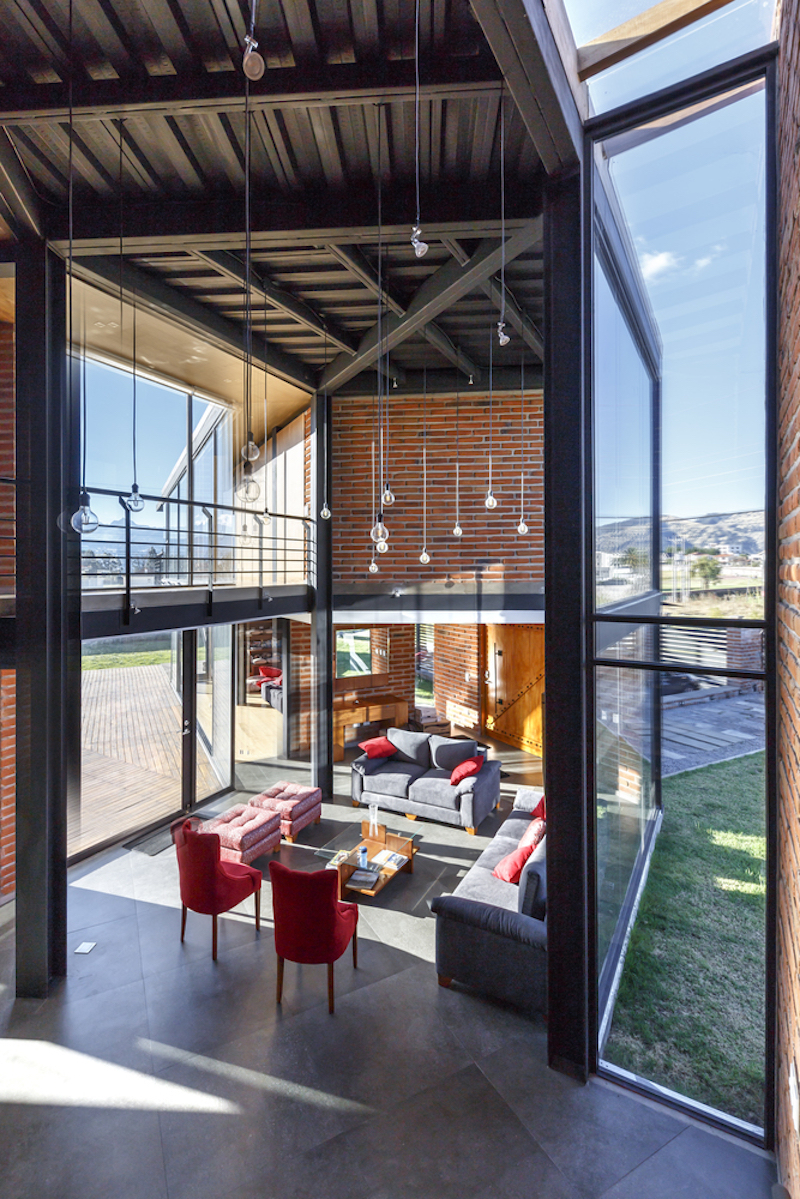 The two wings shape a common social area with a double-height living room, a kitchen and a dining area