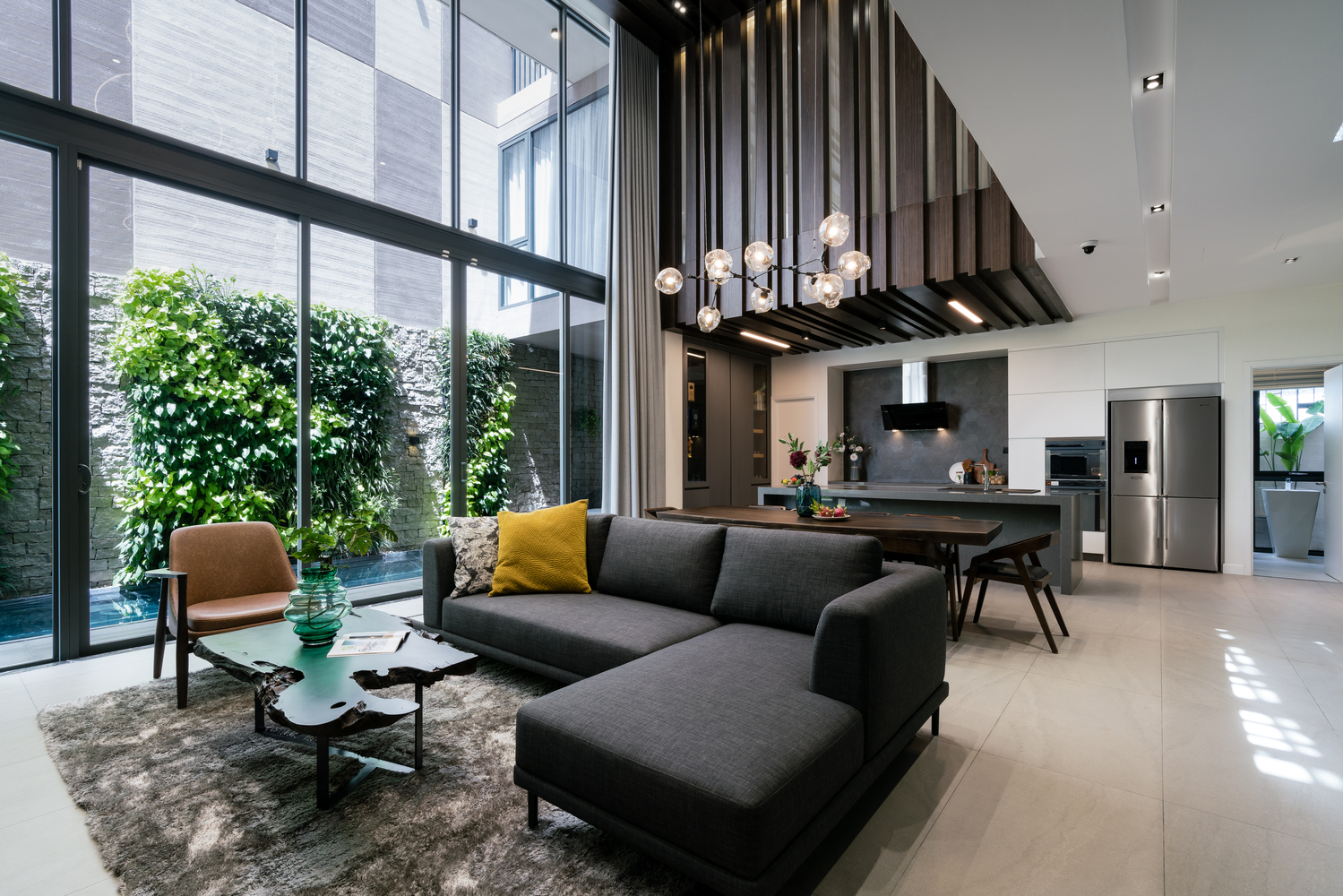 The living area is a double-height volume with a glazed facade facing the pool area