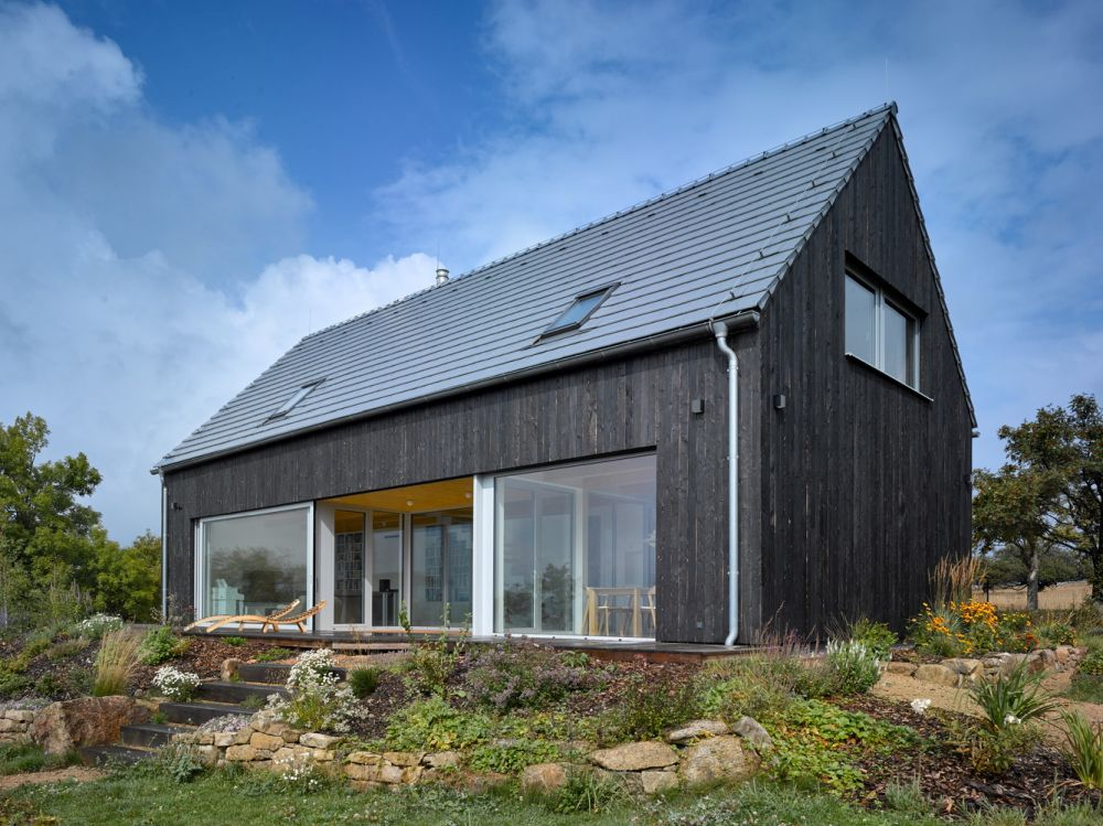 The gabled roof and gray exterior helps the house to blend in and to maintain a traditional appearance