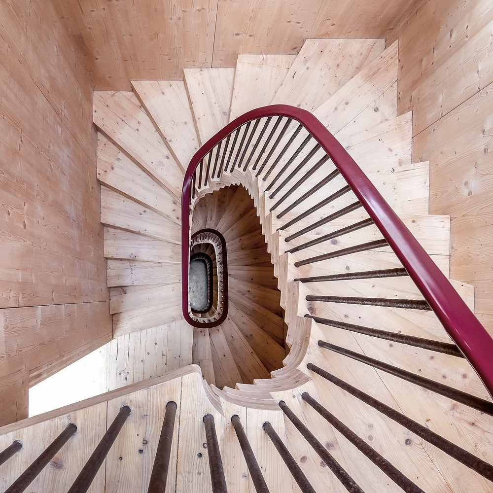 The spiral staircase is built out of timber and attached to the side of the tower