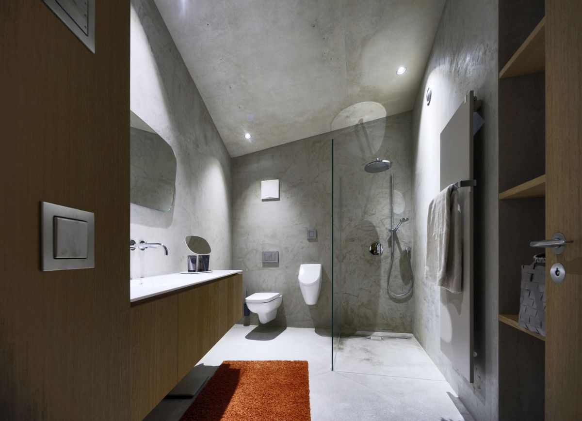In the bathroom, the light coming through the window creates shadowy patterns on the bare concrete walls
