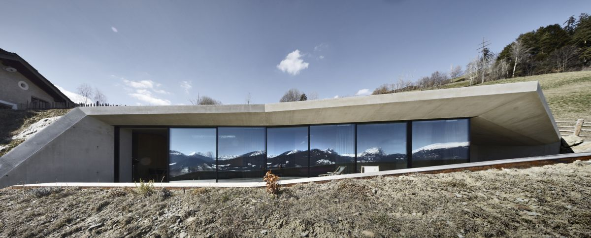 A concrete shell frames the building, forming a covered deck that's facing a gorgeous view