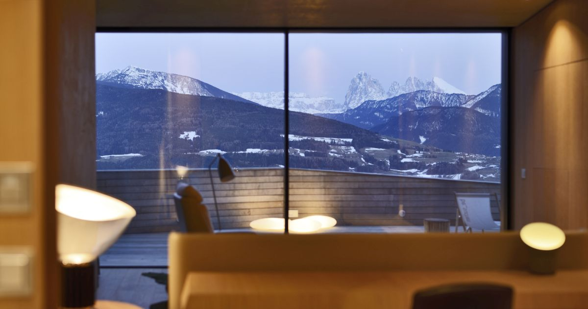 A beautiful valley unfolds beyond the new building's glazed facade, becoming a part of the interior decor