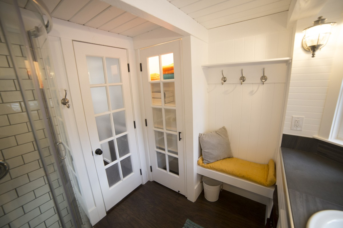 Across from the shower is a nook with a small bench, a shelf and hooks on the wall