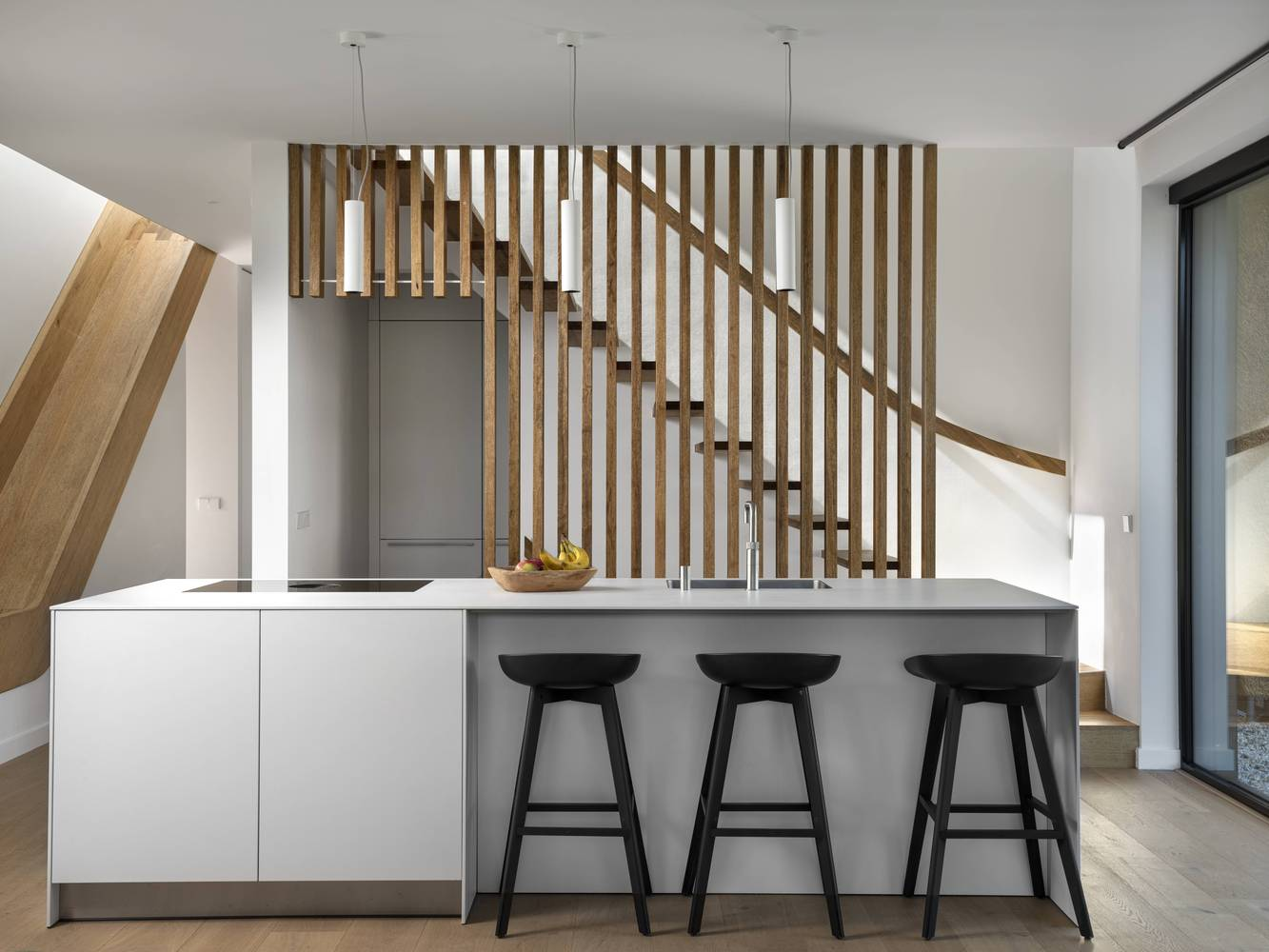 The kitchen is adjacent to the staircase area which includes a custom slide for the kids