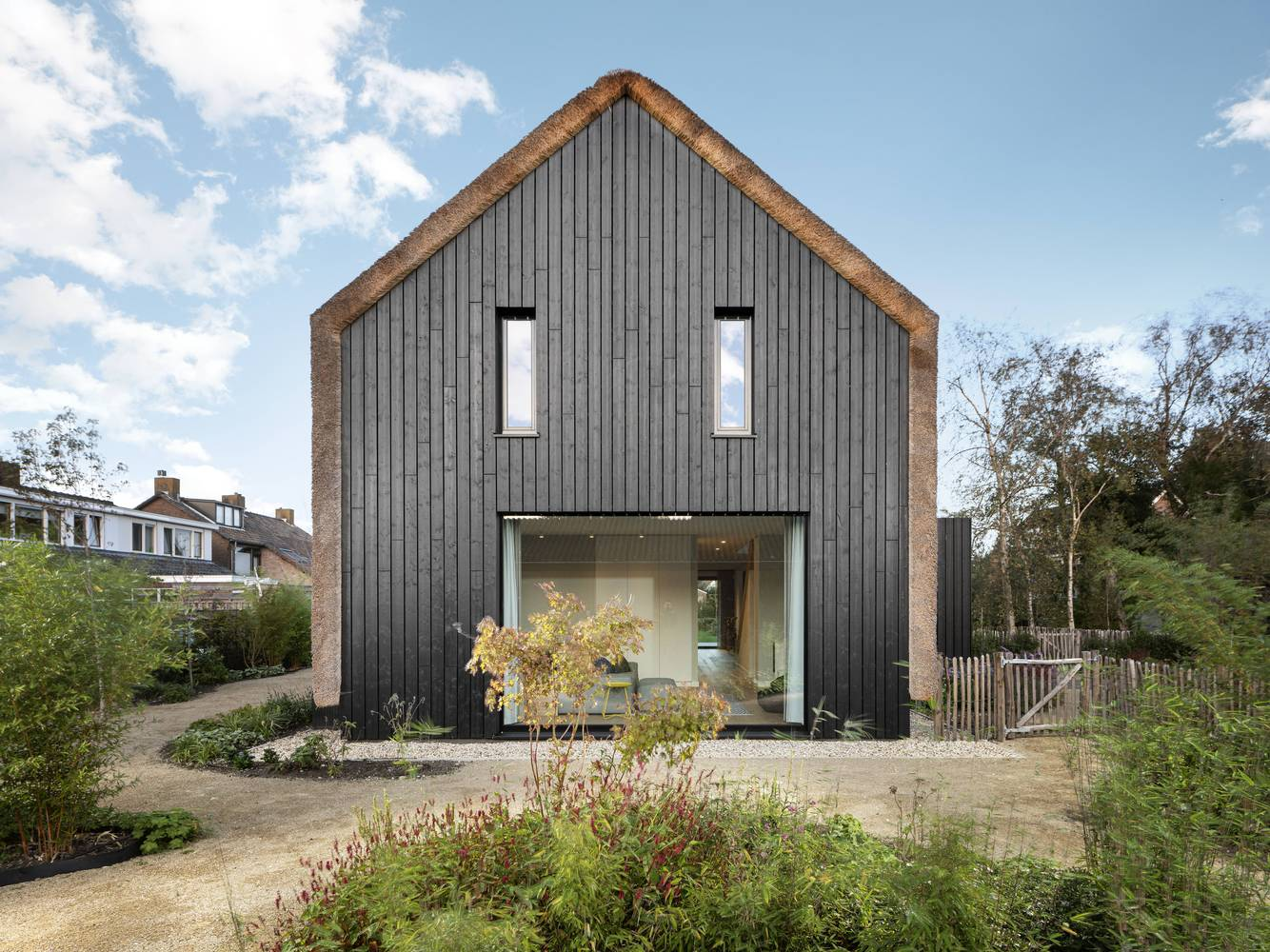 The house has a very simple and classic shape with a roof that seamlessly transitions into walls