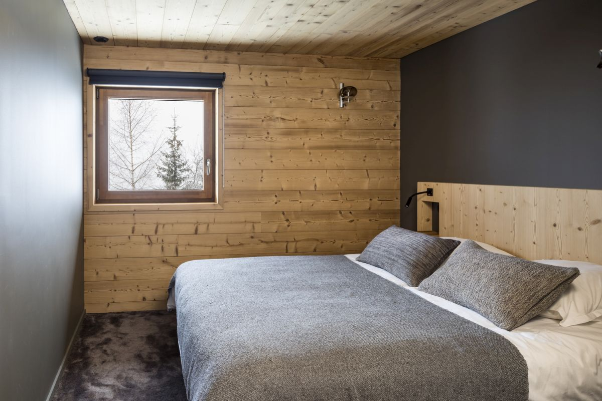 The small, square-shaped window gives this bedroom a very cozy and intimate look