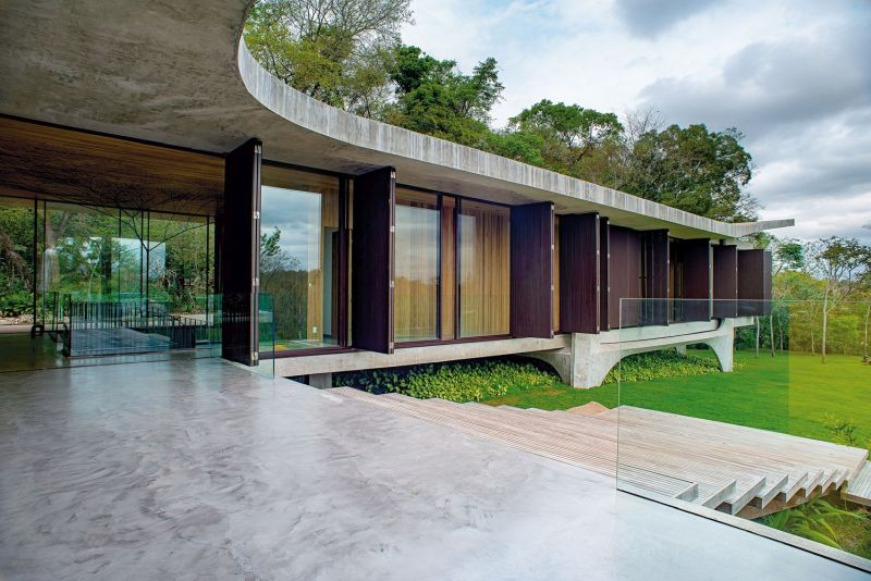 The house has an L-shaped floor plan which extends along two sides of the plot, bordered by the forest