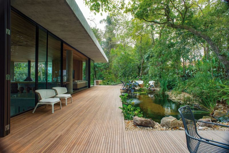 The indoor living areas expand outside through this wooden deck which wraps around the landscape