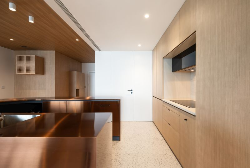 The brushed copper island is the centerpiece of the entire apartment