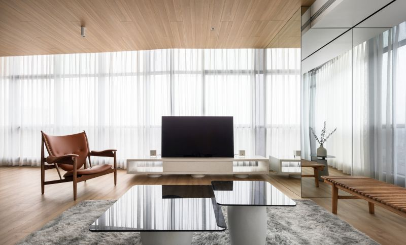 The living area has mirrored walls, full-height windows and minimalist furniture