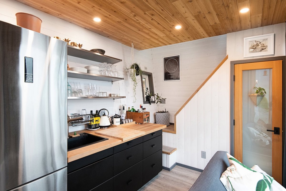 The wood-paneled ceiling and butcher block counter add warmth to the kitchen area