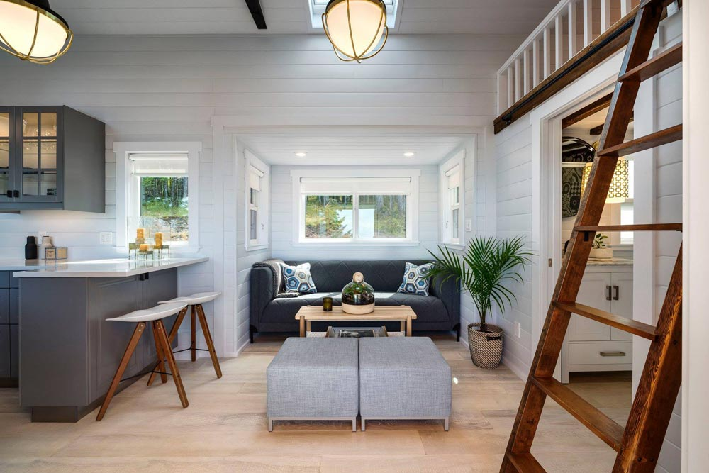 The living area is framed by the kitchen on one side and the bathroom and loft on the other