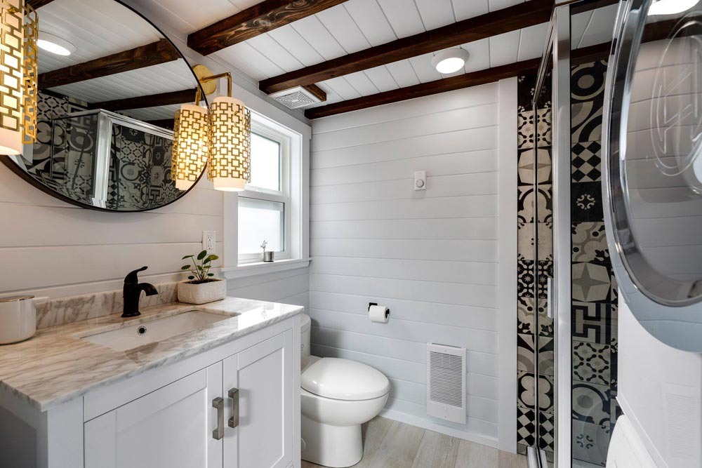 The bathroom also has exposed beams on the ceiling which break the simplicity of the white interior