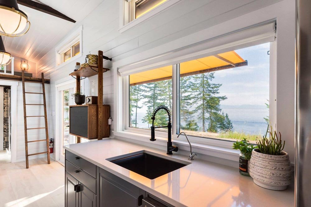 The kitchen window is positioned behind the sink, taking the place of the usual backsplash
