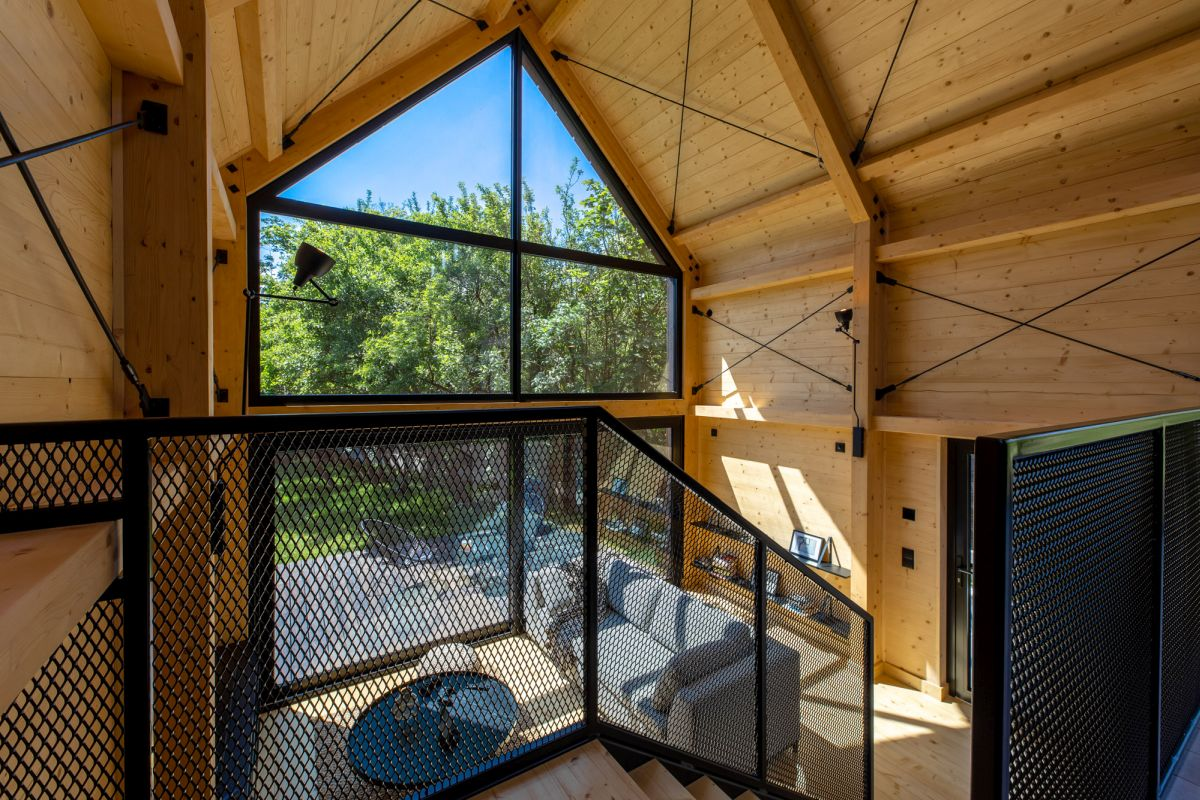 The living room has a double-height ceiling, with windows that go all the way up
