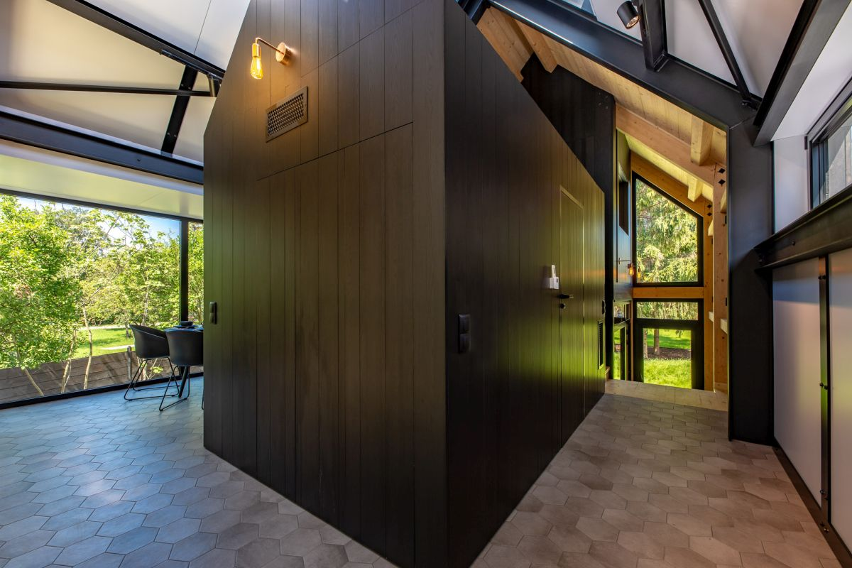 The hexagonal floor tiles ground the upstairs volumes with their warm, earthy color tones