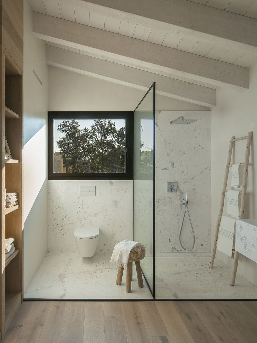 A glass wall between the shower and toilet maintains the open plan.