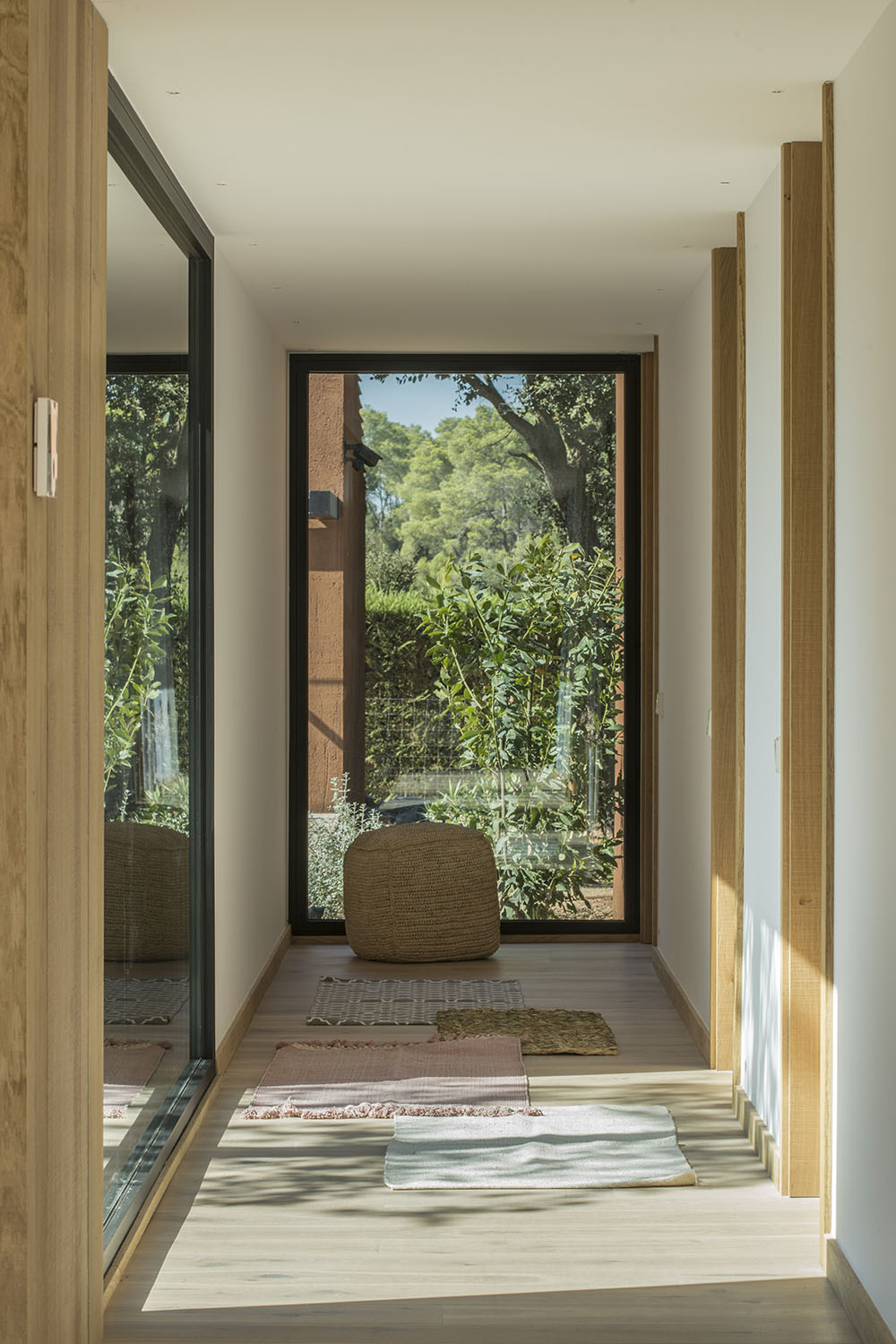 A hallway ends in a large window, leading the eye to the trees outside.
