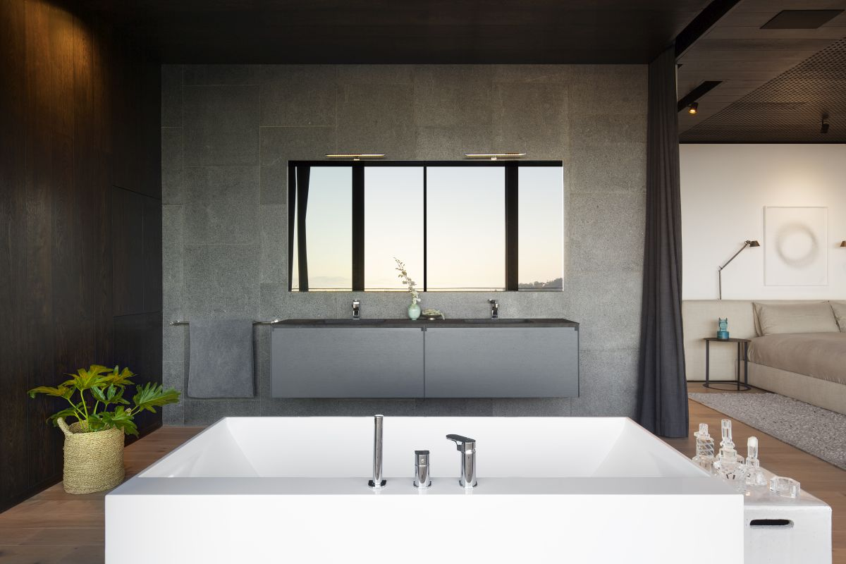 The en-suite bathroom is a natural extension of the bedroom, featuring similar materials and colors