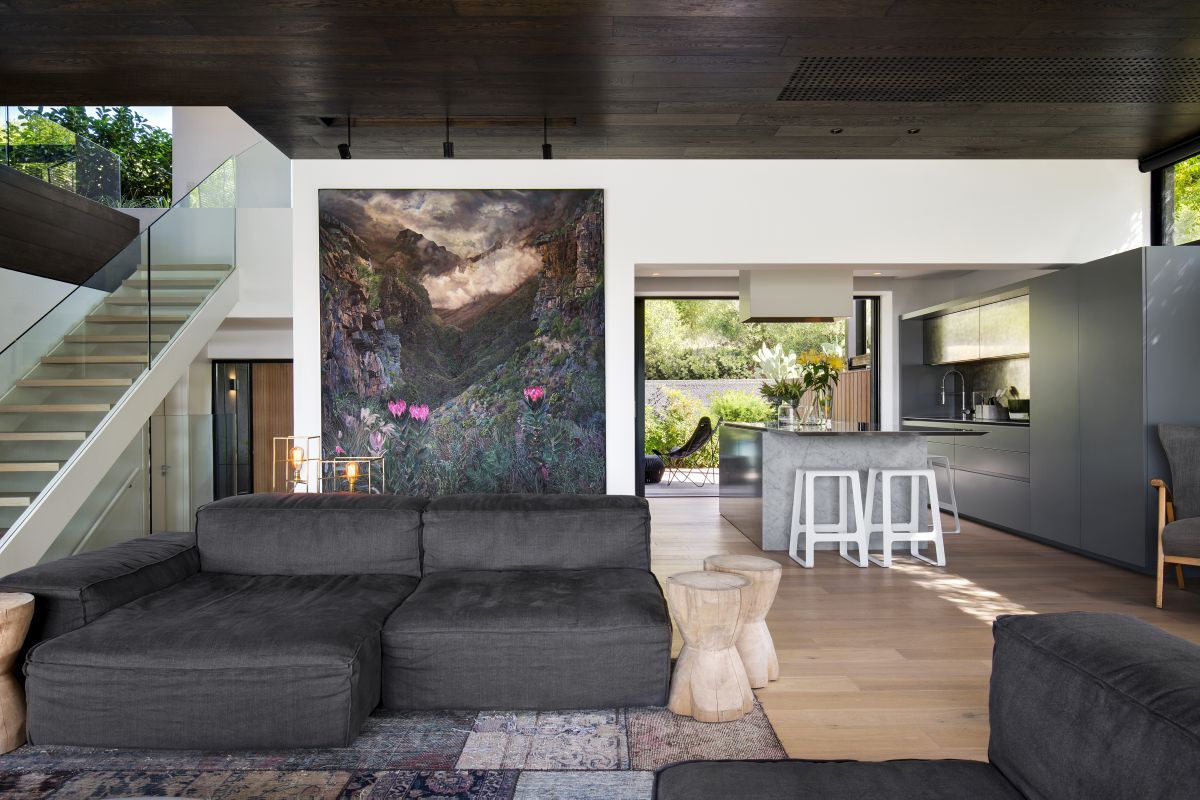 The color palette used in the living area is based on grays and softened by the floral motif of the artwork