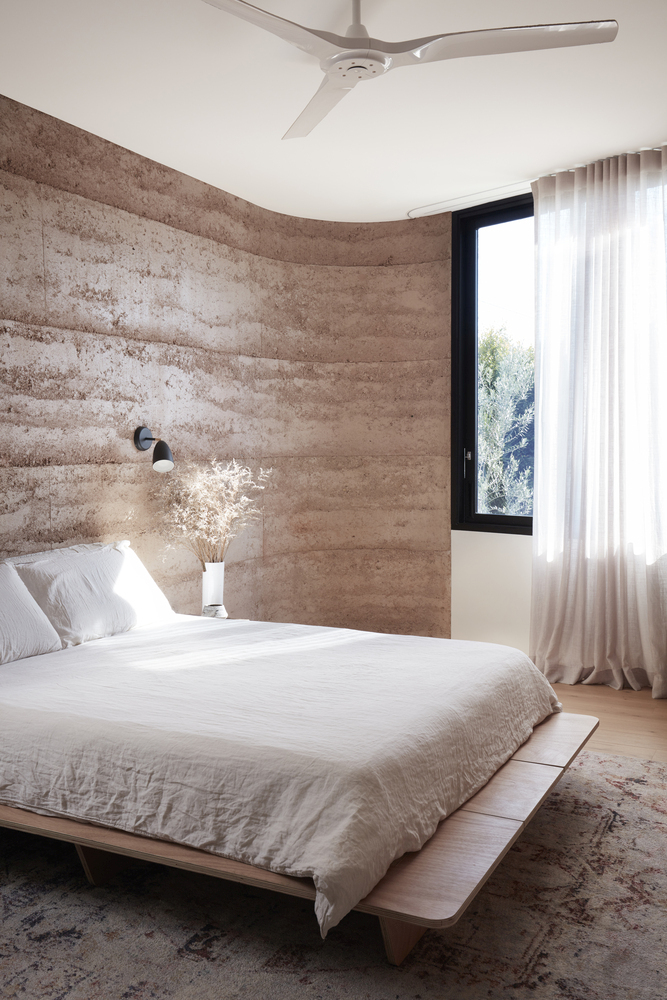 The rammed earth walls and their curved shape makes this bedroom look very cozy