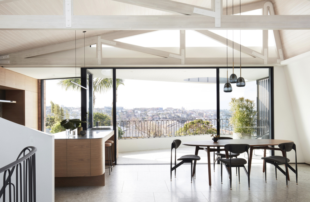 A set of glass doors connects the top floor living areas to a balcony with a spectacular view