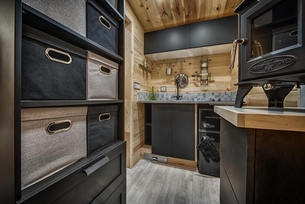 A tall storage cabinet with multiple open shelves doubles as a divider between the living/ sleeping area and the kitchen