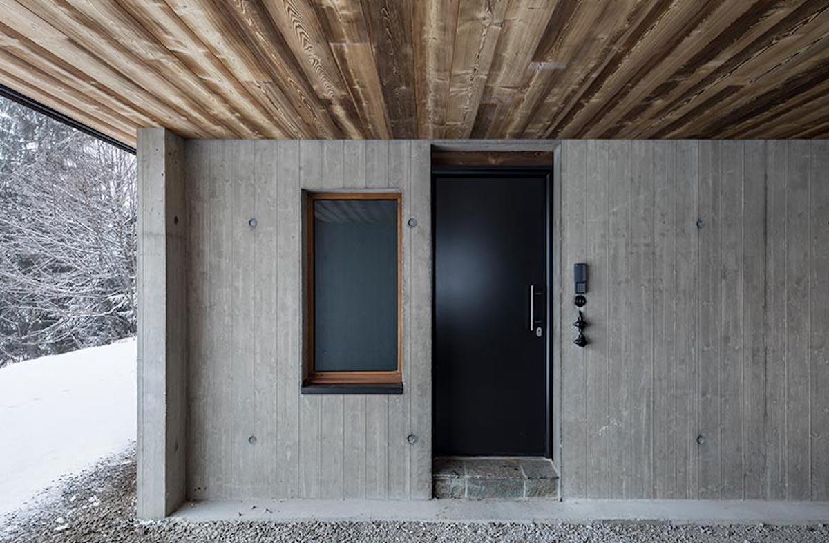 The entrance is positioned on the ground floor, being embedded into the concrete base