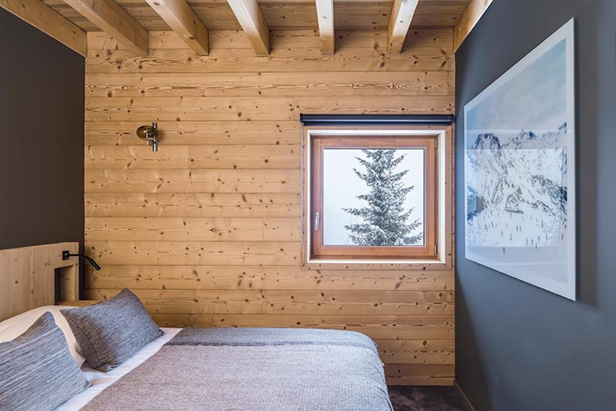 The master bedroom is small as well. It has exposed ceiling beams and a tiny window